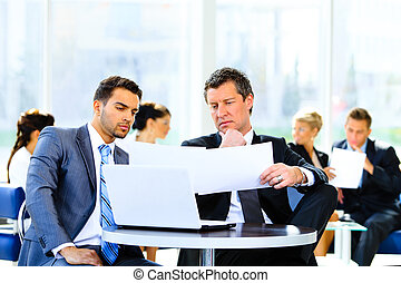 Two confident business people in formalwear discussing something while sitting at the office
