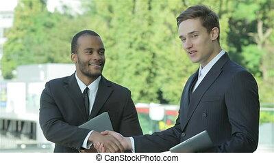 Two confident businessman handshake