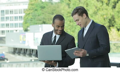 Two confident businessman holding a tablet and a laptop