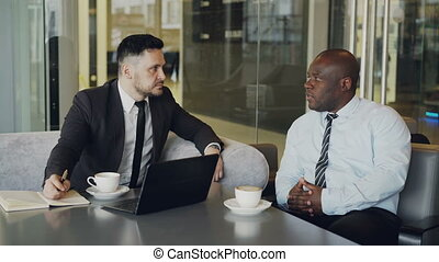 Two confident businessmen discussing about partnership during meeting in modern glassy cafe