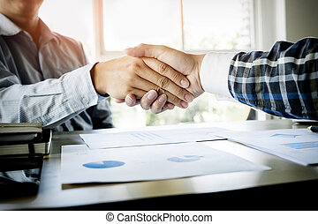 Two confident businessmen handshaking and smiling while sitting at the table together