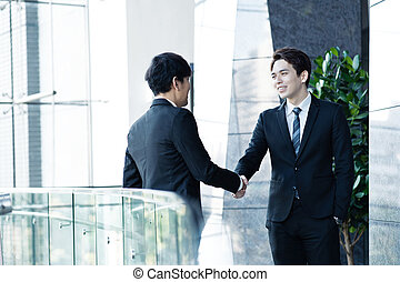 Two confident businessmen shaking hands and smiling