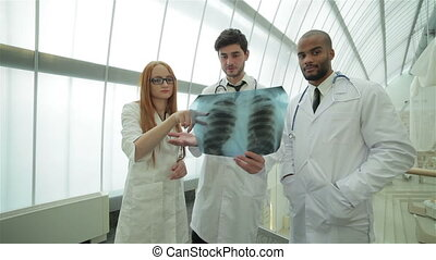 Two confident doctor examining x-ray snapshot of lungs in clinic until the stand