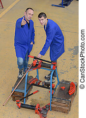 two confident mechanics working at a workshop