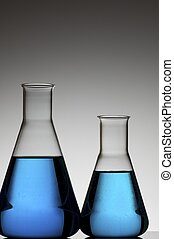 two conical flasks with liquid blue and white background