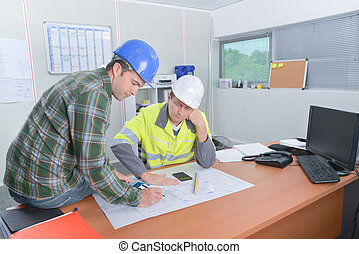 Two construction workers discussing plans