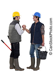 Two construction workers greeting each other