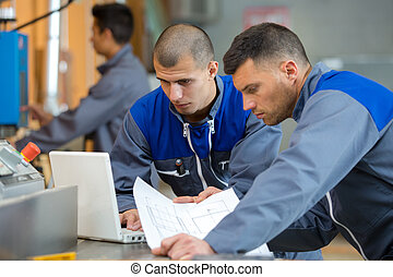 two construction workers holding plans discussing project