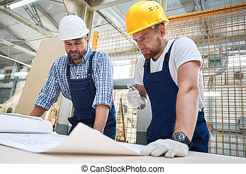 Two Construction Workers Inspecting Plans