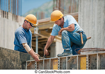 Two construction workers installing concrete formwork frames...