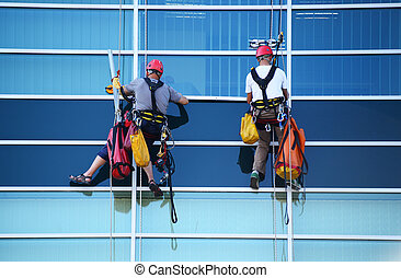 Two construction workers working at height on skyscraper -...
