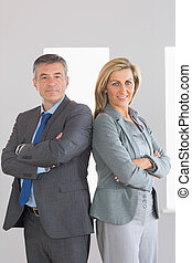 Two content mature businesspeople looking at camera standing firmly back to back with crossed arms at office