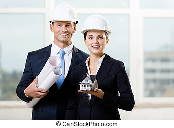Two contractors keeping blueprints and model house - Two...