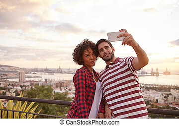 Two cool friends taking a selfie while standing on a bridge...