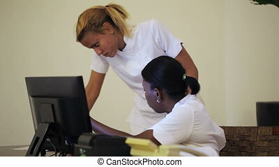 Two cosmeticians in office discussing some documents
