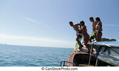 Two Couple Jumping In Water From Long Tail Boat Holding...