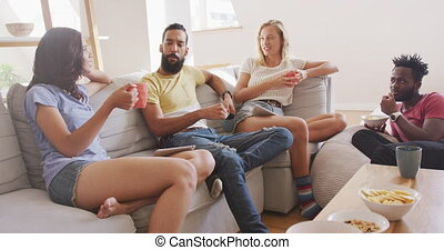 Two couples chatting while having breakfast together at home