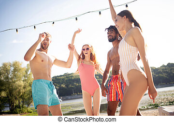 Two couples dancing while chilling outside near pool