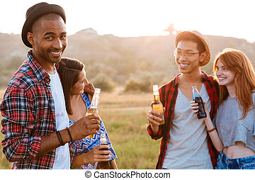 Two couples drinking beer and soda outdoors