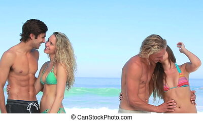 Two couples embracing together on the beach