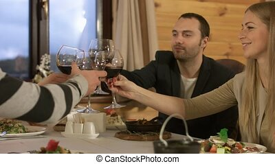 Two couples having dinner and clinking glasses with wine in a restaurant