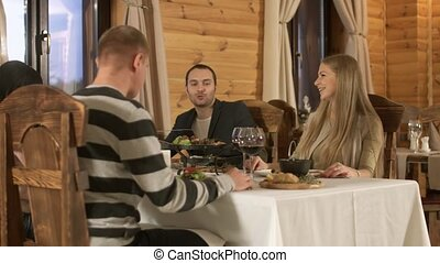Two couples having dinner at restaurant and talk