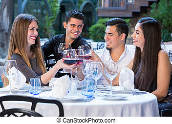 Two couples in garden of restaurant on double date.