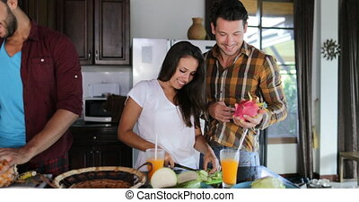 Two Couples In Kitchen Cooking Together, Young Woman And Man Group Talking Cut Vegetables And Fruits Prepare Healthy Meal