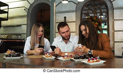 Two couples of friends dressed in summer, who is sitting in a restaurant and waiting for their dishes, selected for lunch.