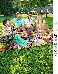 Two couples picnicking in a park