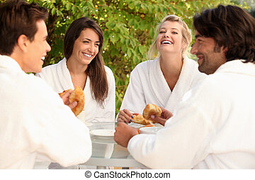 Two couples sharing a joke over breakfast in the garden