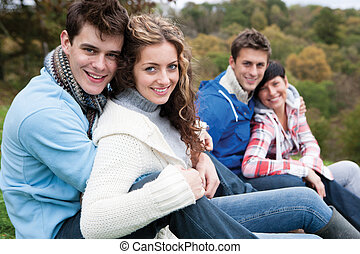 Two couples sit together outside and smile for the camera.