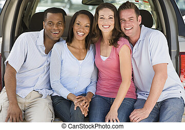 Two couples sitting in back of van smiling