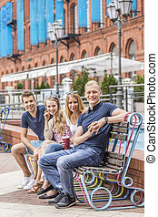 Two couples sitting together on a bench