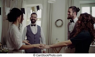 Two couples standing on a indoor birthday party, greeting....