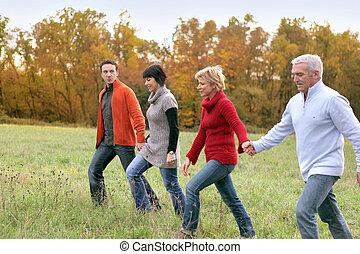 Two couples strolling across a field