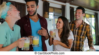 Two Couples Talking In Kitchen Tasting Fresh Juice, Young Man And Woman Drinking Together Happy Smiling