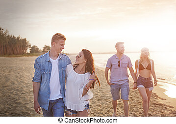 Two couples walking on the beach