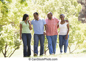 Two couples walking outdoors arm in arm smiling