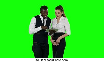 Two coworkers look at a laptop together. Green screen