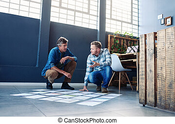 Two coworkers strategizing with papers on an office floor -...
