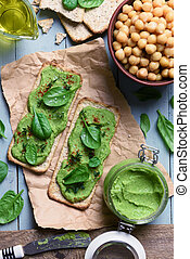 Two crackers with green spinach humus on wooden table. Flat...