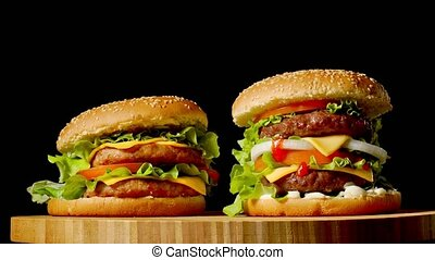 Two craft beef burgers on wooden table isolated on dark...