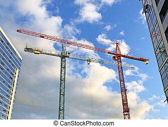 Two cranes next to the building, against the background of the evening sky and clouds.
