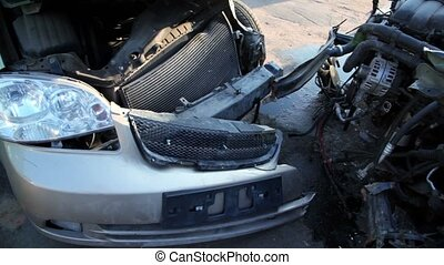 Two crashed cars stand on junkyard, closeup view in motion