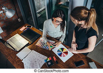 Two creative female designers choosing colors working with colour palette in the office