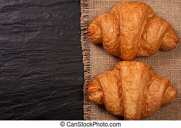 two croissant on black stone background with copy space for your text. Top view