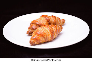 Two croissants on white plate