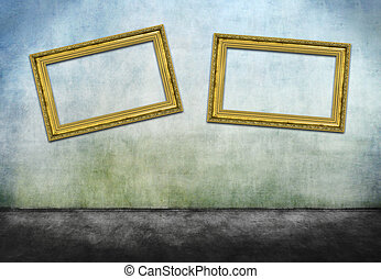 Two crooked golden frames on gray dirty wall