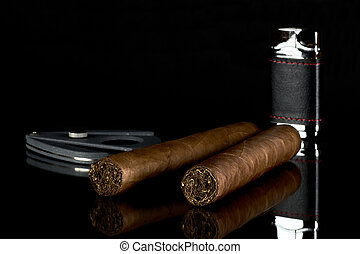 Two Cuban cigars with a lighter and a cutter on a black background